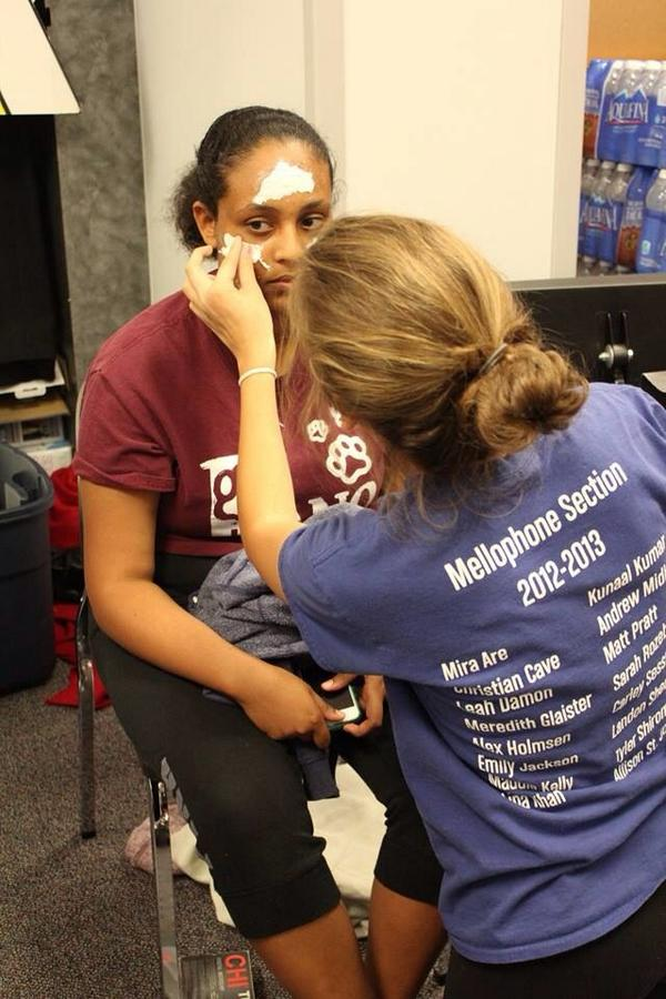 A band member applies makeup to senior Sarah Abdallah before the opening of the haunted hallway. Photo used with permission of Megan Liu.
