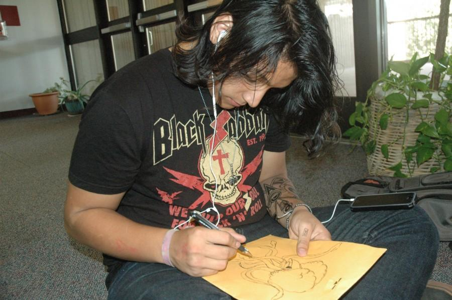 Junior Danny Barrientos draws in the library on Oct. 22. Photo by Ella Hunt.