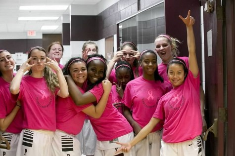 Before the game the girls basketball team poses for a team pic showing off their pink.
