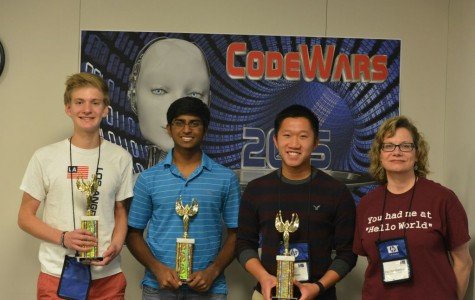 Casey Hopper, Nikhil Pandeti, and Jeremy Doan pose with their CompSci teacher Ms.Gallatin holding their trophies.