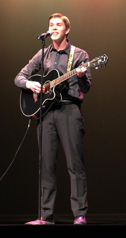 Senior Bryce Baumann strums a song for his talent portion. Photo by Kelly Jones