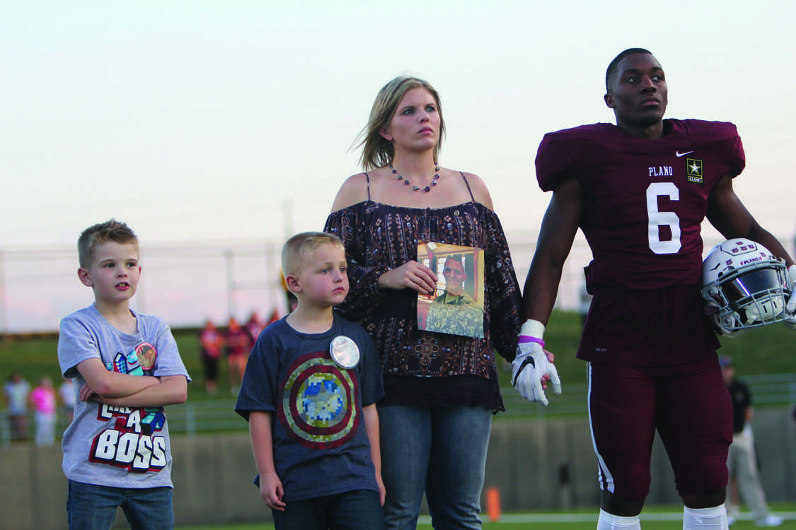 Junior Seagol Mbua stands with the family of First Lieutenant Robert Welch III during Plano's Maroon Out game against MacArthur. (Photo by Jordyn Carter)