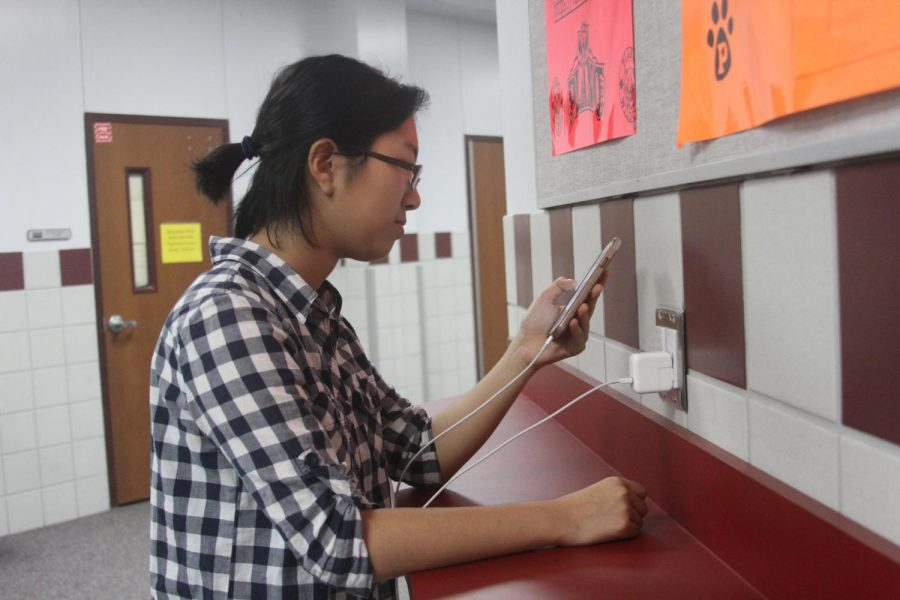 Senior Wendy Chu uses the study stations in B building to charge her phone during after school hours
