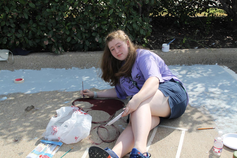 Senior Jillian Walker works on painting her parking spot.