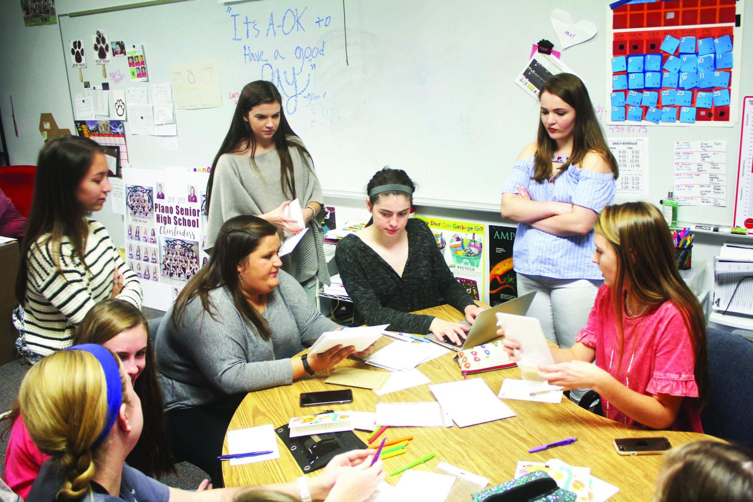 Senior Caitlyn Pierce, Claire McKinney, Megan Manly, Elyse Young, Kaylee Willman and juniors Sarah Bruner and Anna Smith write letters for Caring Cats.