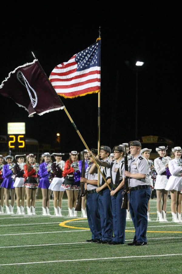 Senior Ethan Ortega, senior Alia Diamon, and junior Ryan Hurst hoist the flag for the Pledge of Allegiance before a game.