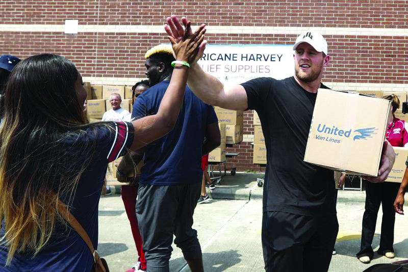 Houston Texans hero, JJ Watt high fives a fan as he helps to load boxes for hurricane relief. (photo by Getty Images, used with permission)