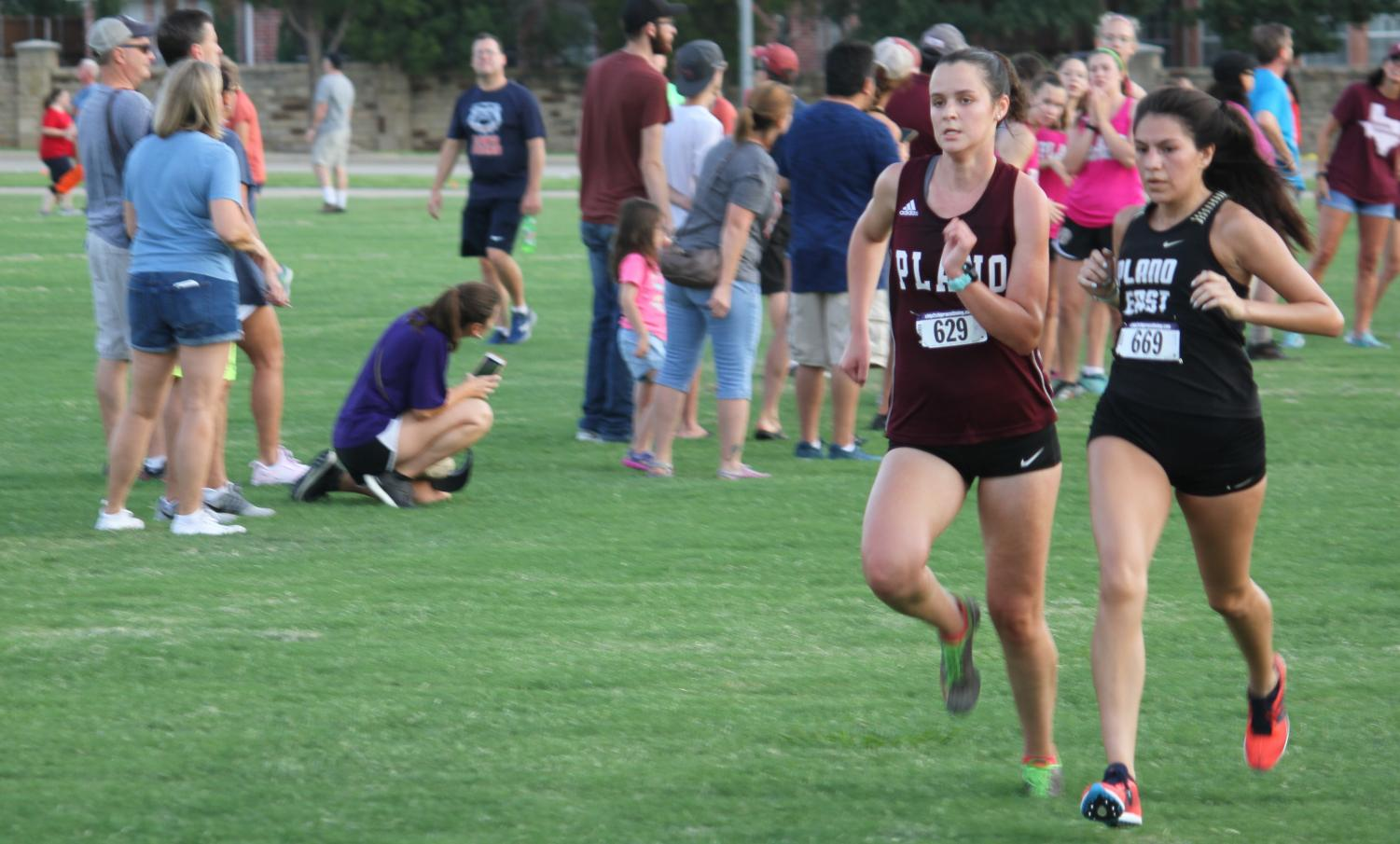 Brooke Dixon pushes herself to get past a runner for Plano East at the Plano Invitational Cross Country meet.
