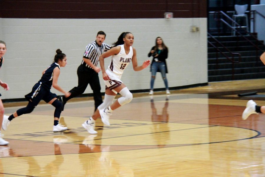 Player number 12, Jordyn Meriitt, chasing after her team while playing defense.