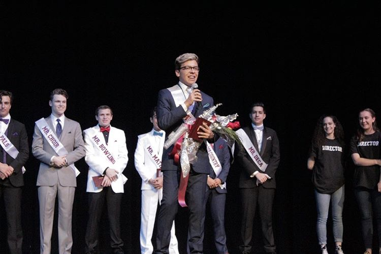 Mr. Plano winner senior Cesar Mendoza accepting his prize front stage with the other contestants behind him.