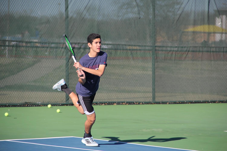 Freshman Herman Aguirre swings at Wildcat tennis court.