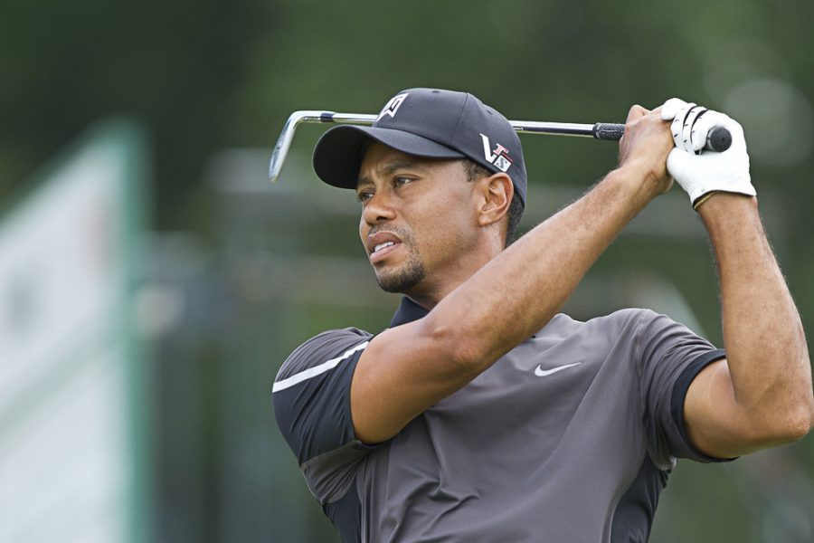 Tiger Woods completing a follow through after a powerful swing of his club.
