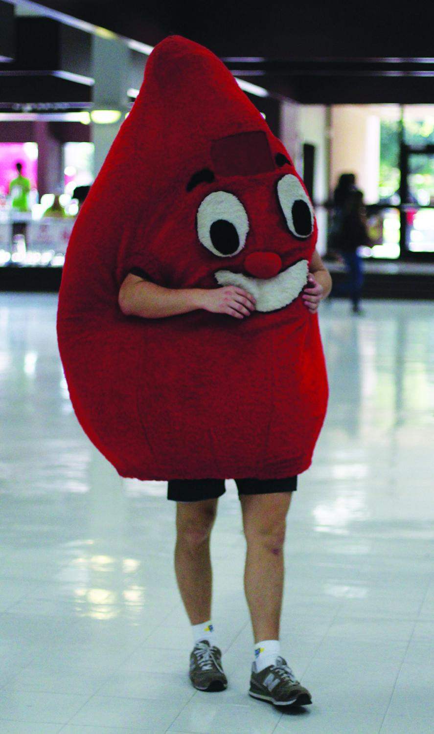 Student in BloodCare blood drop character suit entertains students waiting their turn to give blood.