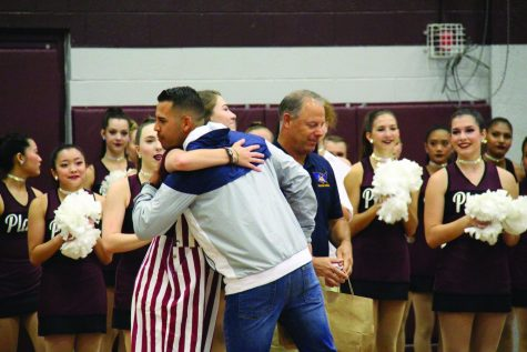 Senior Lily Ray and Eastwood coach Julio Lopez hugging during the combined pep rally.