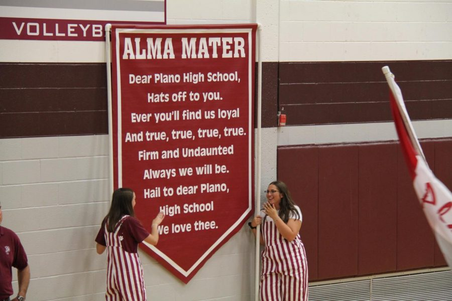 Gina Furman (right) and Kelsie Cameron (left) lift the alma mater high at the pep rally.