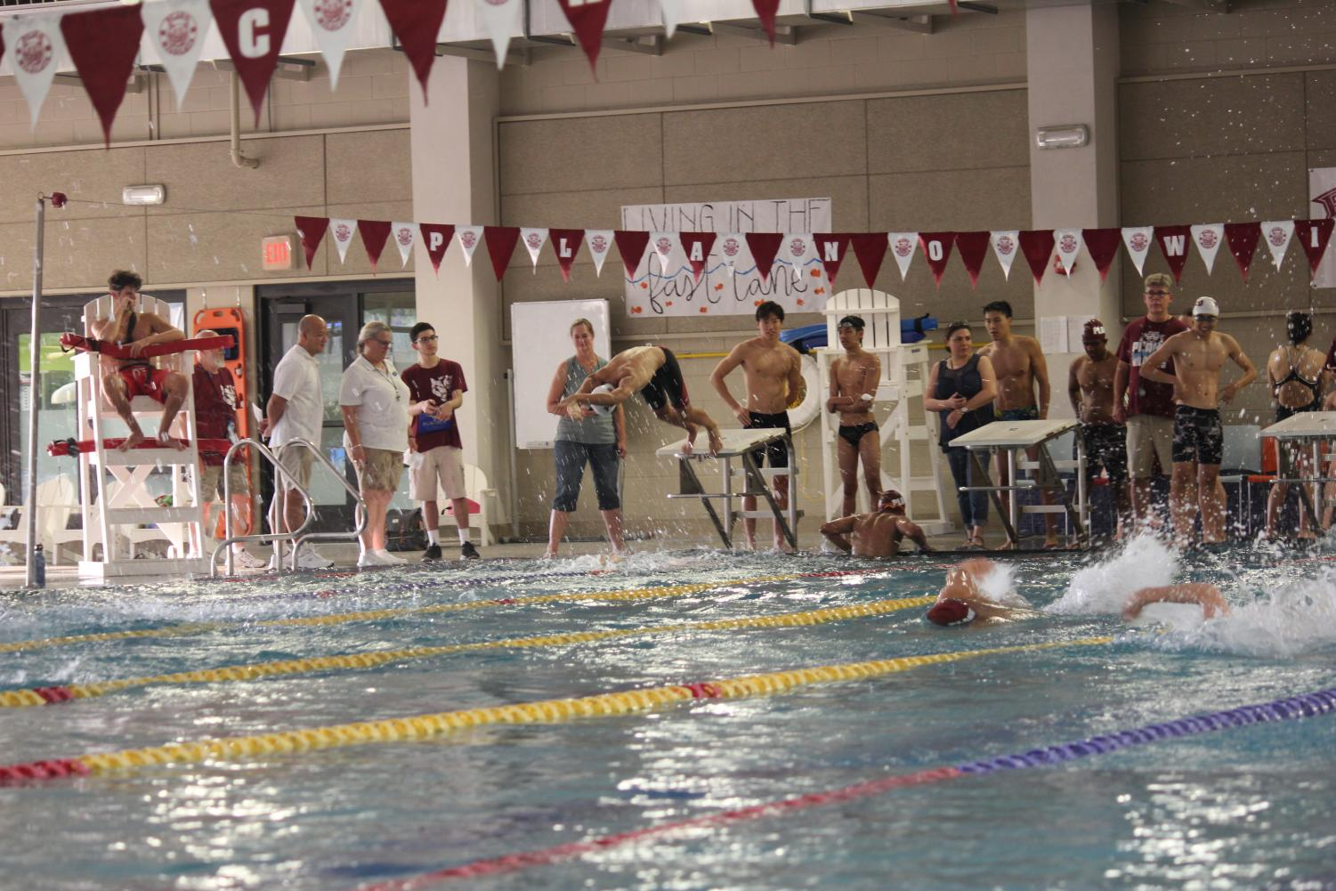 Swimmers launching off diving board in race during intersquad meet.
