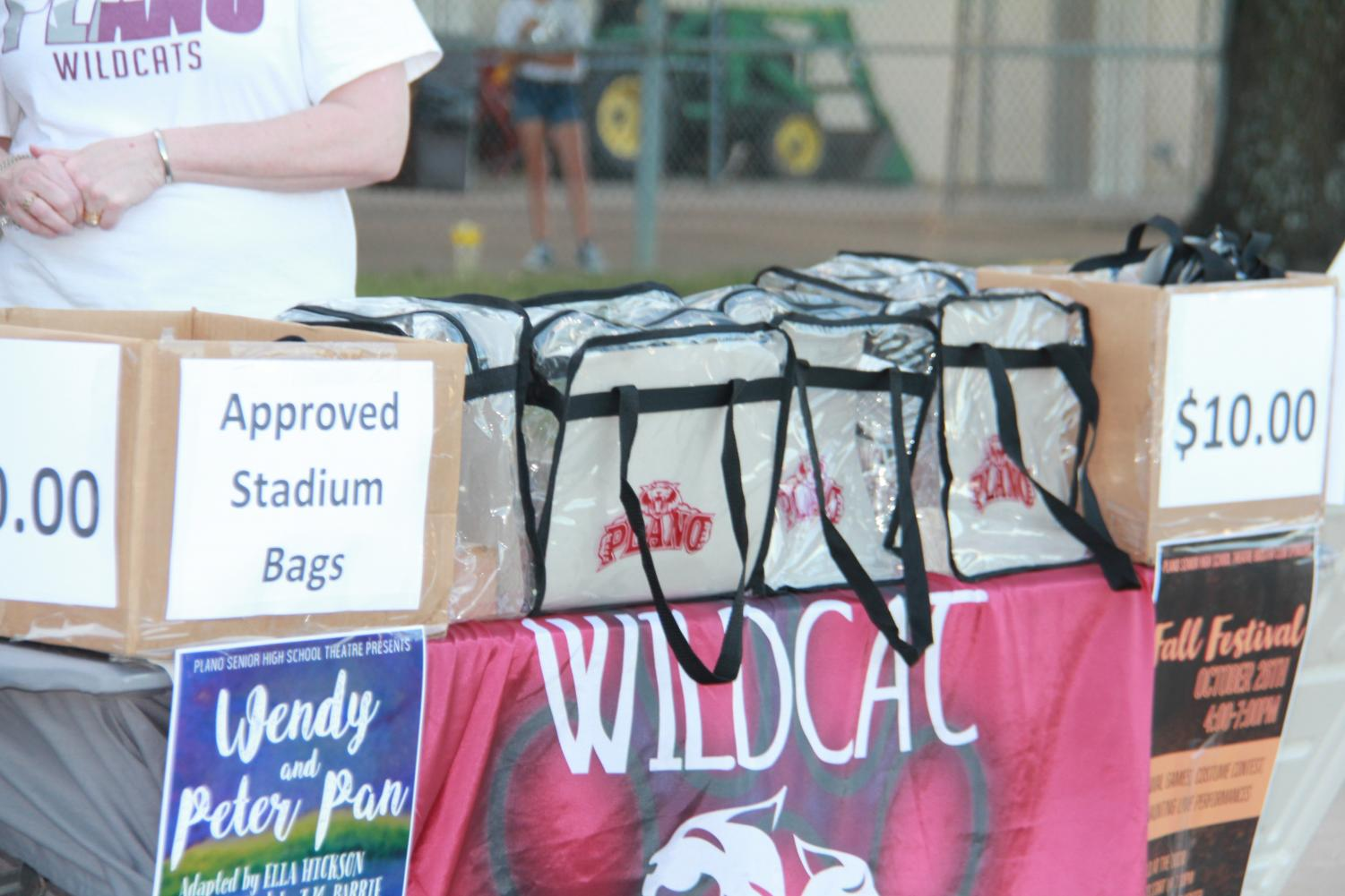 Wildcat football volunteers pass out clear bags allowed into the stadium.