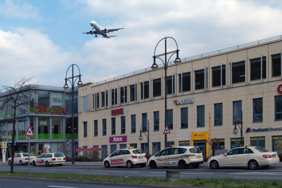 Airplane taking off over a building at an airport in France.