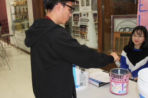Nick Reed donating to the Journey of Hope with STUCO member Devina Setino.