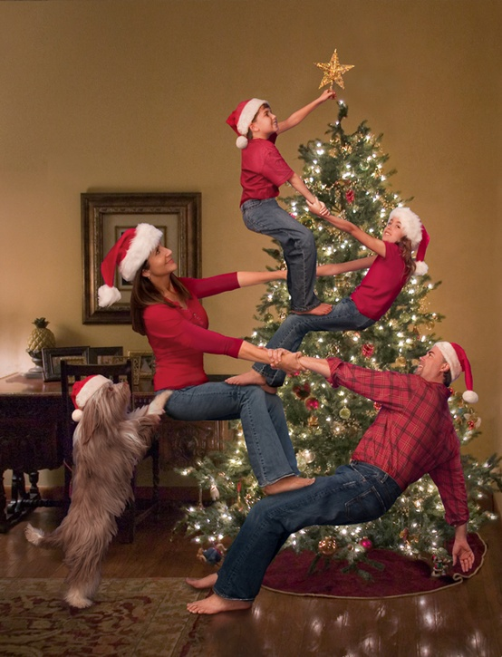 A family celebrating Christmas by decorating the tree all together enjoying the holiday.