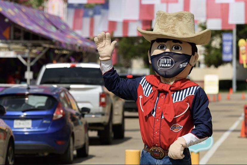 Big Tex waves to fair participants in their cars.